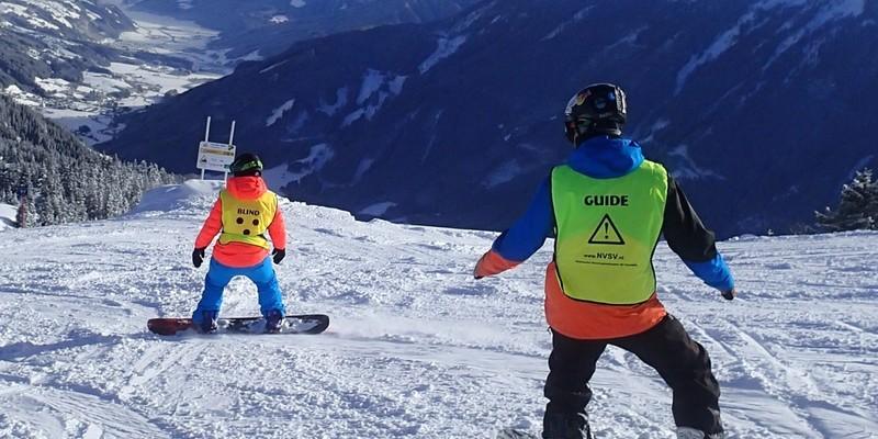 Blinde snowboarder met begeleider